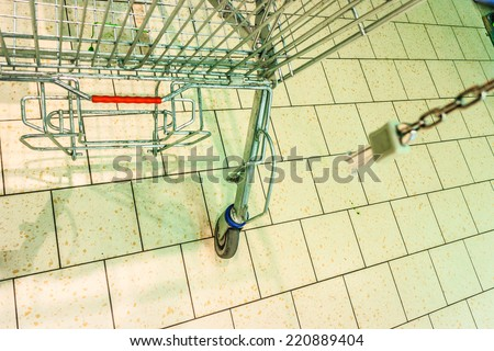 Closeup of empty metal shopping trolley cart on tiled floor in grocery store supermarket.