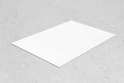 Closeup of empty white rectangle horizontal poster mockup lying diagonally on neutral grey concrete background. Flat lay, isometric view. Blank Template for Corporate Identity