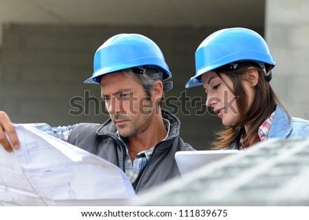 shutterstock closeup of engineers reading plan on building site