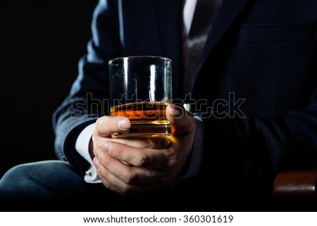 Closeup of executive holding  whiskey to illustrate executive privilege concept #360301619