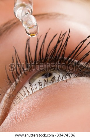 Closeup of eyedropper putting liquid into open eye
