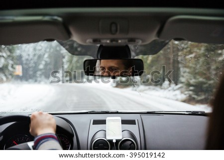 Closeup of eyes of young man reflected in car rear viewer while driving in winter forest