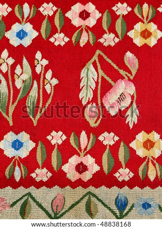 Closeup of fabric carpet pattern with colorful floral ornament on red background.Stylized to folk art style.