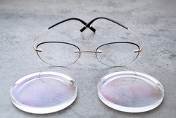 Closeup of fashion trendy eyeglasses lying on table in optical store with new lenses. Professional production, manufacturing and adjust of new glasses lens in optics. Eyewear concept