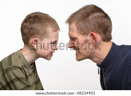 closeup of father and son with angry faces close together