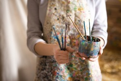 Closeup of female artist hand holding paintbrush