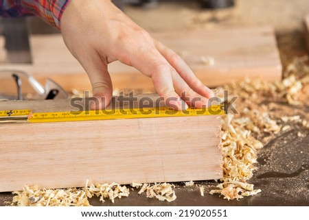 Closeup of female carpenter\'s hand measuring wood with scale in workshop