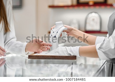 Closeup of female client wearing a white blouse checking the costly necklace designed with blue stones presented by a jewelry store woker wearing white gloves on a glass counter of a jewelry shop.