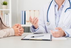 closeup of female doctor explain disease treatment solution for patient in clinic. selective focus photo.