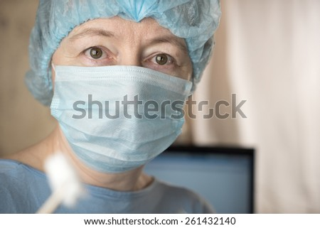 Closeup of female doctor wearing medical mask and surgical cap looking seriously and worried at patient