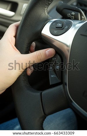 Closeup of female driver adjusting cruise control system on steering wheel #663433309