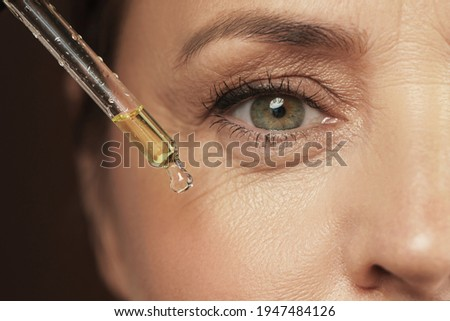 Closeup of female eye and dropper with rejuvenating serum Photo stock ©