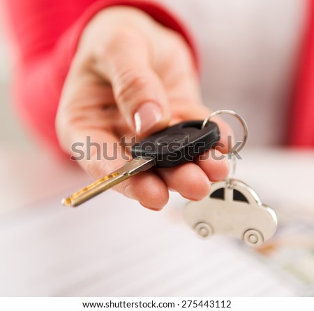 Closeup of female hand giving car key to buyer in automotive dealer\'s office. Auto rent, sale and inspection concept. Shallow depth of field.