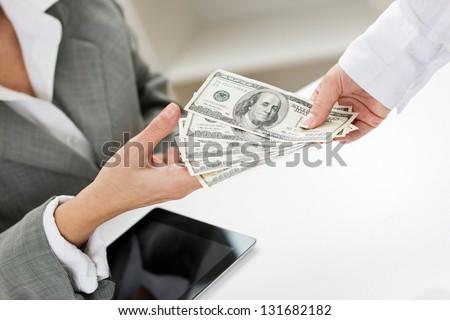 Closeup of female hand giving money.