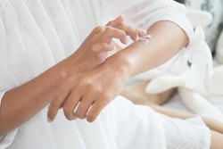 Closeup of female hands applying cream on her arm. Make up, healthy skin, beauty shot, cute asian woman concept