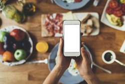 Closeup of female hands holding modern smartphone with blank screen for your text message or design, order food online concept, mock-up of mobile phone, tasty breakfast on the background