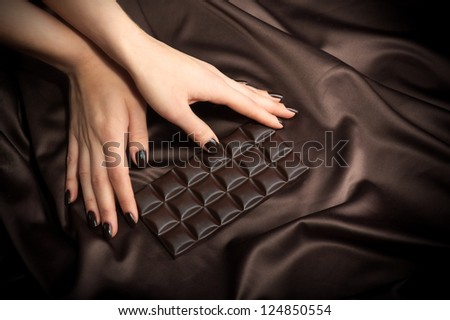 Closeup of female hands touching the dark chocolate bar