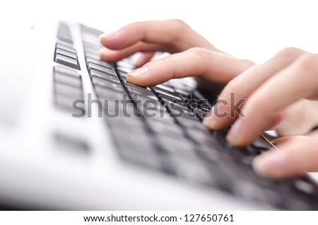 Closeup of female hands typing on keyboard. Shallow dof.
