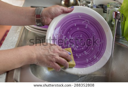 Closeup of female hands washing dish ware by spounge, indoor horizontal shot