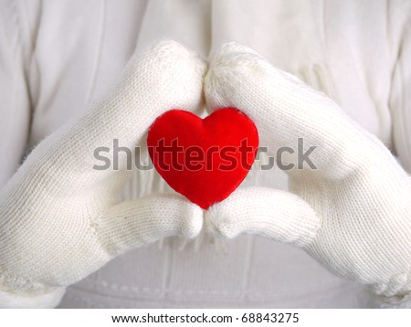 Closeup of female hands wearing white warm wool gloves holding read suede heart as Valentine's Day concept