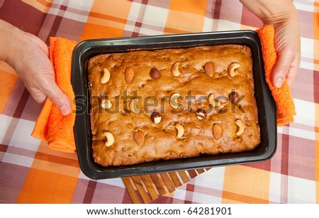 Closeup of female hands with fresh  honey cake. One of the stages of cooking of  honey cake.  See series