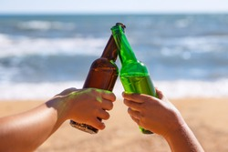 closeup of female hands with glass bottles of beer making toast with sea on the background