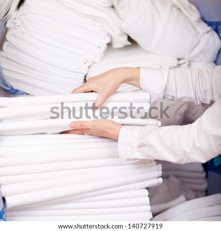 Closeup Of Female Housekeeper\'S Hands Stacking Sheet In Stock Room