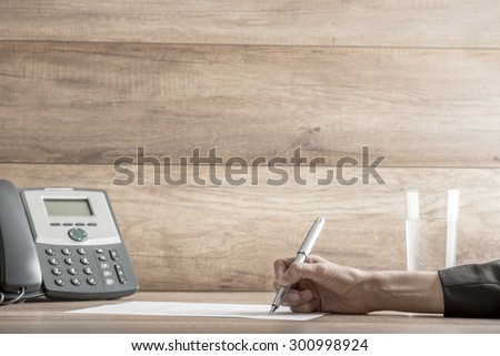 Closeup of female lawyer or executive signing a contract, placed on desk, near the telephone, with copy space on wooden wall.