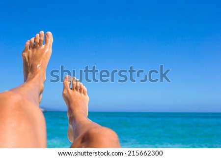 Closeup of female legs background of the turquoise sea #215662300