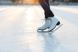 Closeup of  female legs in white old fashion skates on outdoor ice rink. Young woman skating on frozen lake in snowy winter park on sunset time
