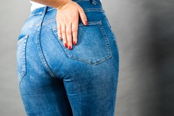 Closeup of female plus size hips buttocks wearing blue jeans, woman presenting fashionable outfit. Fashion clothing femininity concept. Gray background