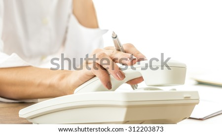 Closeup of female secretary or telephone operator hanging or picking up white telephone receiver while holding an ink pen.