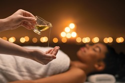 Closeup of female therapist applying massage oil on hands before therapy, young black lady lying on massage table at spa