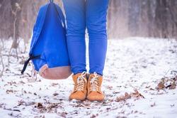 Closeup of female winter orange shoes on snow