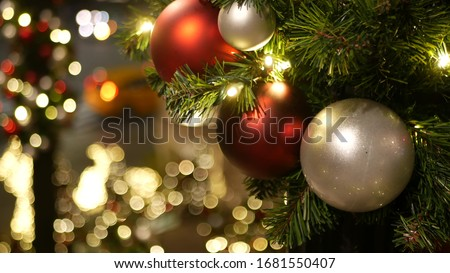 Closeup of Festively Decorated Outdoor Christmas tree with bright red balls on blurred sparkling fairy background. Defocused garland lights, Bokeh effect. Defocused night city street, cars on road. stock photo