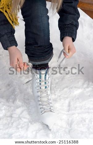 closeup of figure skating ice skates, girl puts on the skates