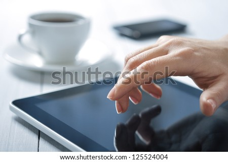 closeup of finger touching screen on tablet-pc with shallow depth of field