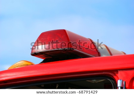 Closeup of fire truck top lights against blue sky background.
