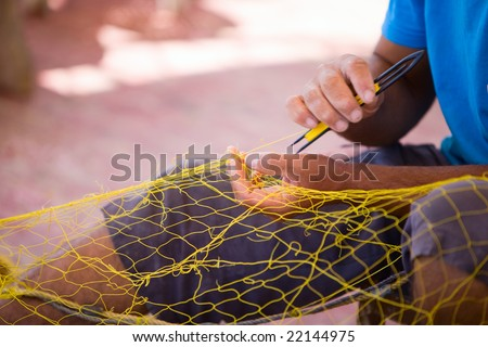 Closeup of fisherman repairing fishing net