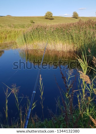 Closeup of fishing rod during fishing time near river. Sunny, beautiful water picture about fishing with green grass, blue water and fisherman equipment.