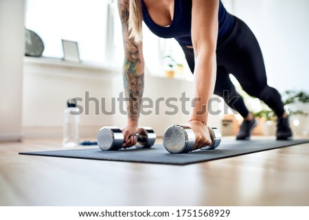 Photo of  Closeup of fit woman doing pushups strength exercise during home workout