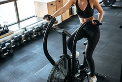 Closeup of fitness woman working out on spinning bicycle in gym