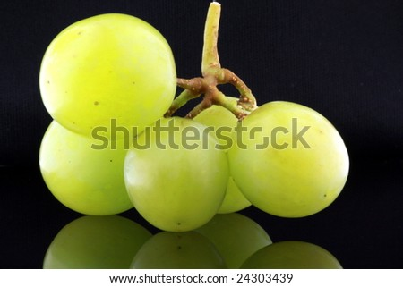 closeup of five green grapes reflecting on black background