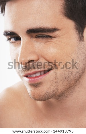 Closeup of flirtatious young man winking on white background