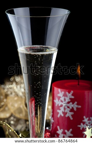 Closeup of flutes of champagne, candles and Christmas decoration on black background.