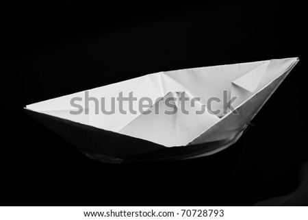 Closeup of folded paper ship against black background with selective focus