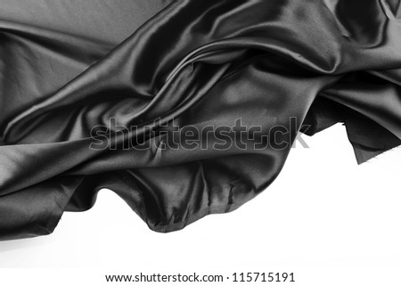 Closeup of folds in black silk fabric on white background - stock photo