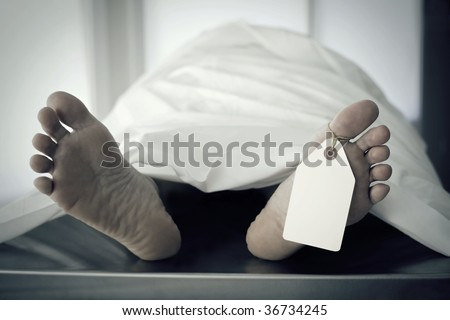 Closeup of foot in a morgue with blank tag hanging from the big toe.