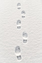 Closeup of footsteps in snow going forward