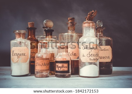 closeup of former apothecary pots with ingredients for medicine isolated over dark background. translation : terpine powder, Drosera and aubepine tincture, kola tincture, Iris essential oil, morphine